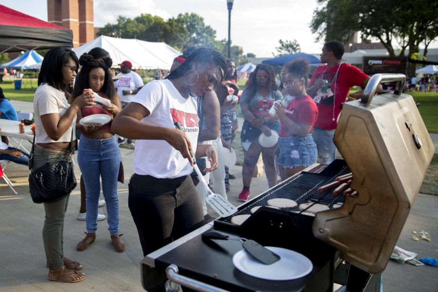 Cincinnati sophomore Faith Berry checks on the hamburgers at the Campus Activities Board tailgate before the WKU vs Rice football game on Thursday, Sept. 1, 2016 on South Lawn. Ebony Cox/HERALD