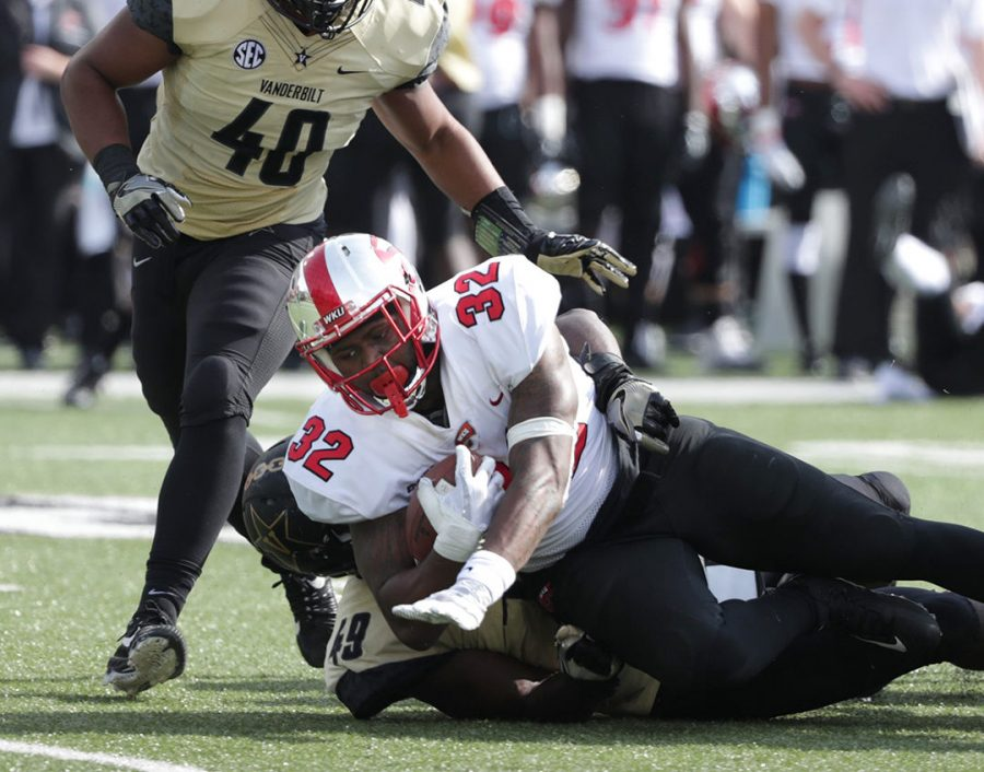 WKU running back D'Andre Ferby (32) is brought down by Vanderbilt defensive lineman Jonathan Wynn (49) at Vanderbilt Stadium on Saturday, November 3