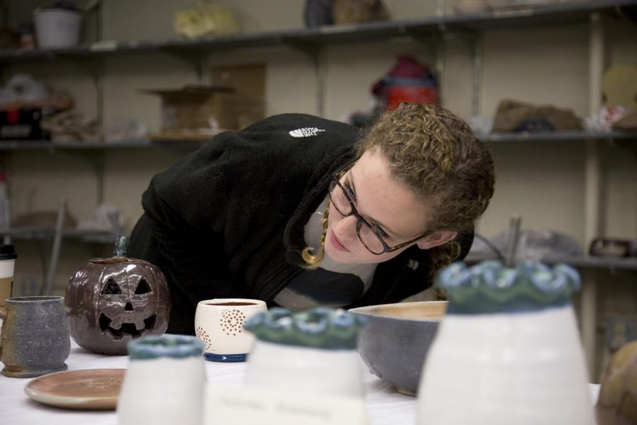 McKenna Webb, a junior from Crestwood, Ky. inspects pottery during the Clay Club sale in FAC on Monday, Nov. 13, which featured art from students in ceramics at WKU. Senior Kathryn Moore, who helped organize the event, says that she enjoys the sale because