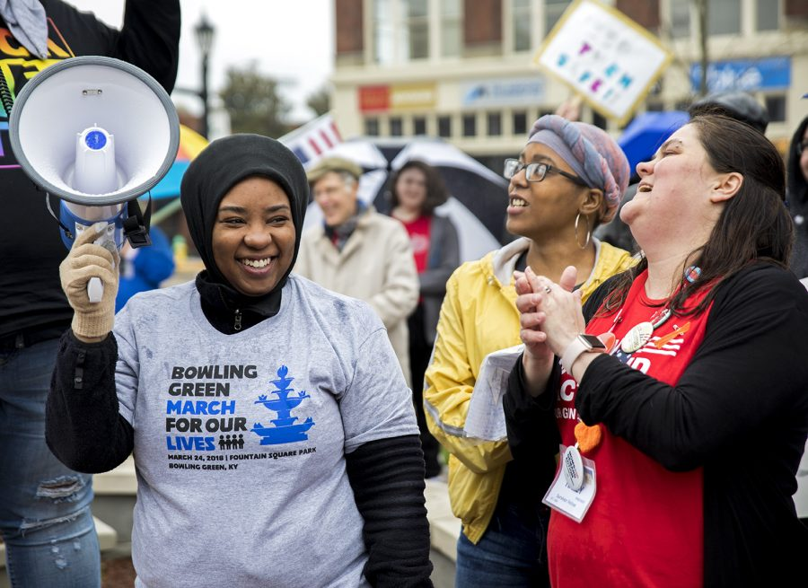 """Bowling Green resident and member of Black Lives Matter and Moms Demand Action Chastity Dunn (left) Bowling Green High School student Hasana Graham (center), 16, and Bowling Green resident Haley Rinehart (right) cheer as people speak to the crowd during the March for Our Lives rally in downtown Bowling Green on March 24. """"I'm afraid to go to school because you never know what's going to happen,"""" Graham said."""
