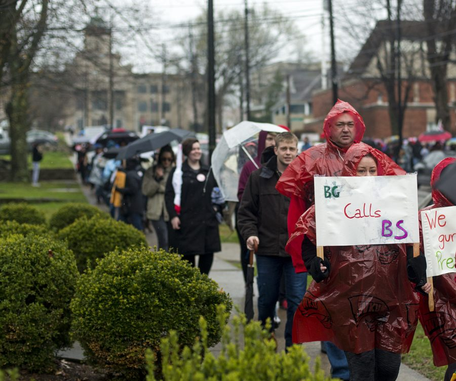 """Protestors walk down College Street during Bowling Green's March For Our Lives, advocating for gun control. Protestors held signs and participated in chants, including """"books not bullets"""" on their route from Cherry Hall to Bowling Green's town square."""