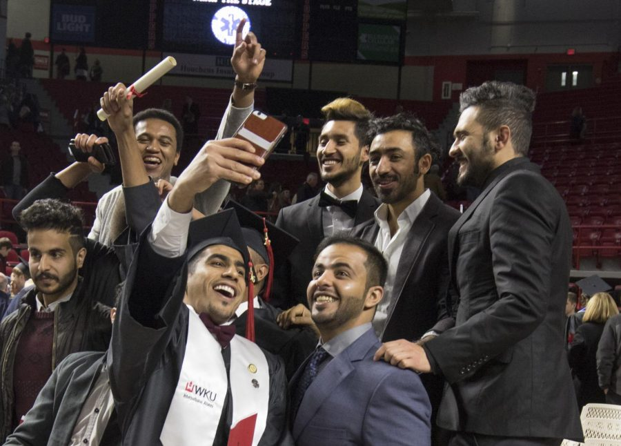 A new graduate takes a celebratory selfie with friends and other graduates during the commencement ceremony on Saturday, December 10th, in Diddle Arena.