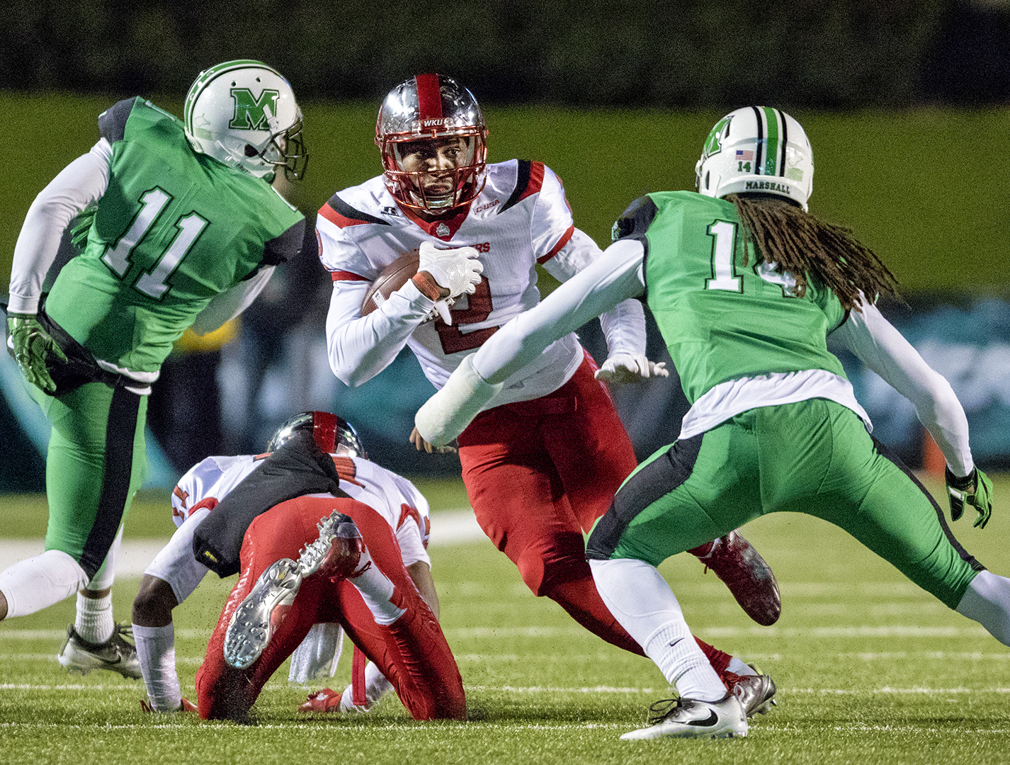 WKU wide receiver Taywan Taylor (2) tries escape a tackle by Marshall University safety Kendall Gant (14) during the Hilltoppers 60-6 win over Marshall on Saturday, Nov. 26th, 2016 at Joan C. Edwards Stadium in Huntington, WV. Evan Boggs / HERALD