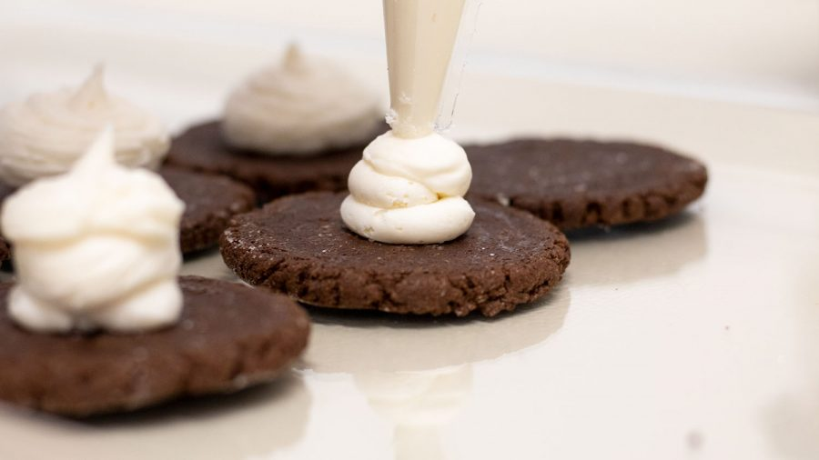 Alison Taylor, owner of Little Fox Bakery, squeezes cream fi lling onto her homemade Oreo cookies, a twist on the classic treat.