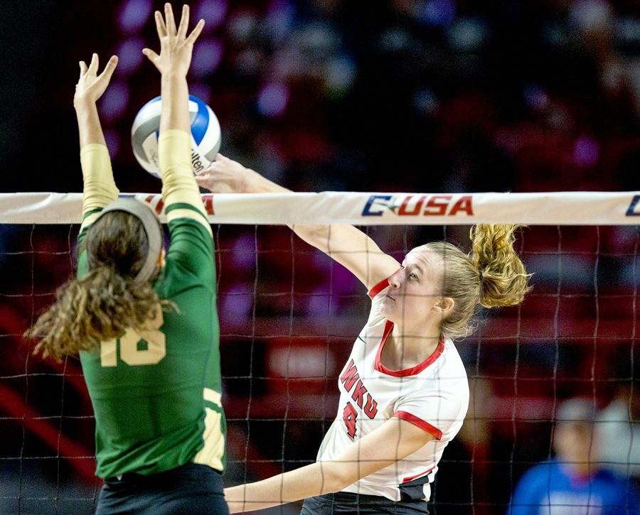 WKU junior Rachel Anderson (4) spikes the ball into the arms of Charlotte sophomore Jocelyn Stoner (18) in the first game of the C-USA Championship Tournament. WKU went on to sweep the tournament, winning it for the fourth year in a row.