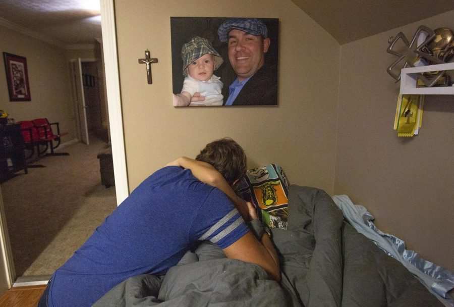 Danette Idlett hugs her son Evan Neel, 10, after spending some time in the boys' bedroom before they went to bed on Wednesday, September 26, 2018 . Idlette co-founded Life's Better Together in memory of Aaron Neel, Evan's father, their portrait together hangs above his bed. Aaron died of a rare lymphoma at age 35.