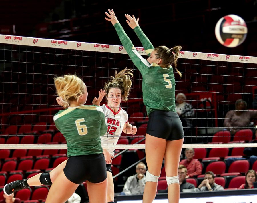WKU's Hallie Shelton (12) hits the ball past the UAB defense during a match at Diddle Arena on October 12, 2018.