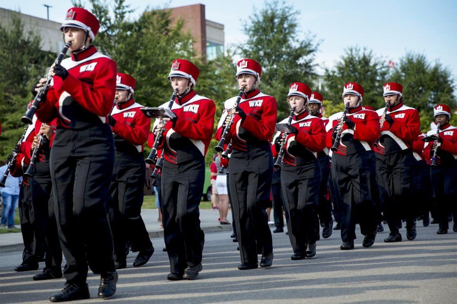 The Big Red Marching Band marches down the street to the stadium before the Hilltoppers game again Rice University on Thursday September 1, 2016 at L.T. Smith Stadium.