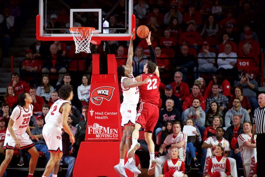 WKU's Charles Bassey (23) blocks Wisconsin's Ethan Happ (22) on Dec. 29 in Bowling Green. Bassey finished the win with four blocks.