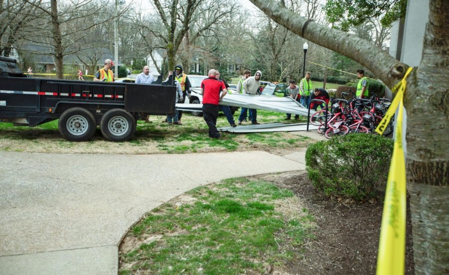 Movers remove the damaged roofing of Bemis Lawrence Hall building on the bike racks near the entrance on Thursday, March 14.