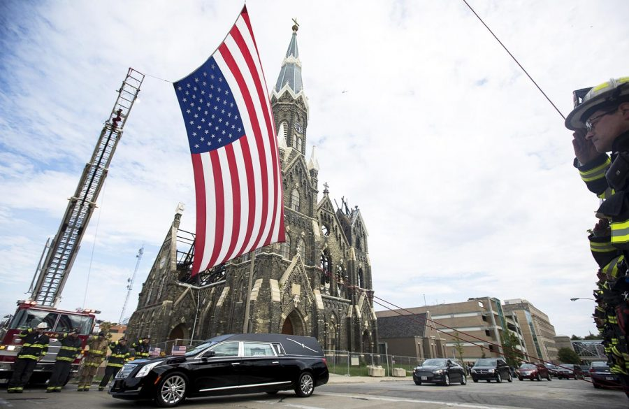 Officer Charles Irvine Jr., 23, lies in a hearse as he is escorted by the Milwaukee Police Department and saluted by the Milwaukee Fire Department as he passes beneath the American flag on Friday, June 8, 2018.