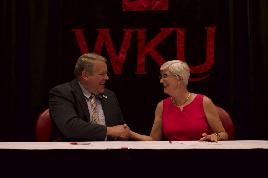 Somerset Community College President and CEO Carey Castle, left, shakes hands with WKU Provost Cheryl Stevens after signing an agreement to join WKU into the University Center of Southern Kentucky.