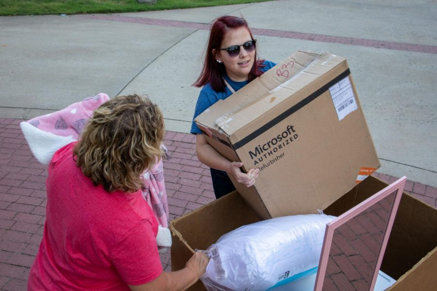 Dawna Price and her former foster daughter Alex fill a box with belongings. Price says this is her third time moving a child of hers into WKU.