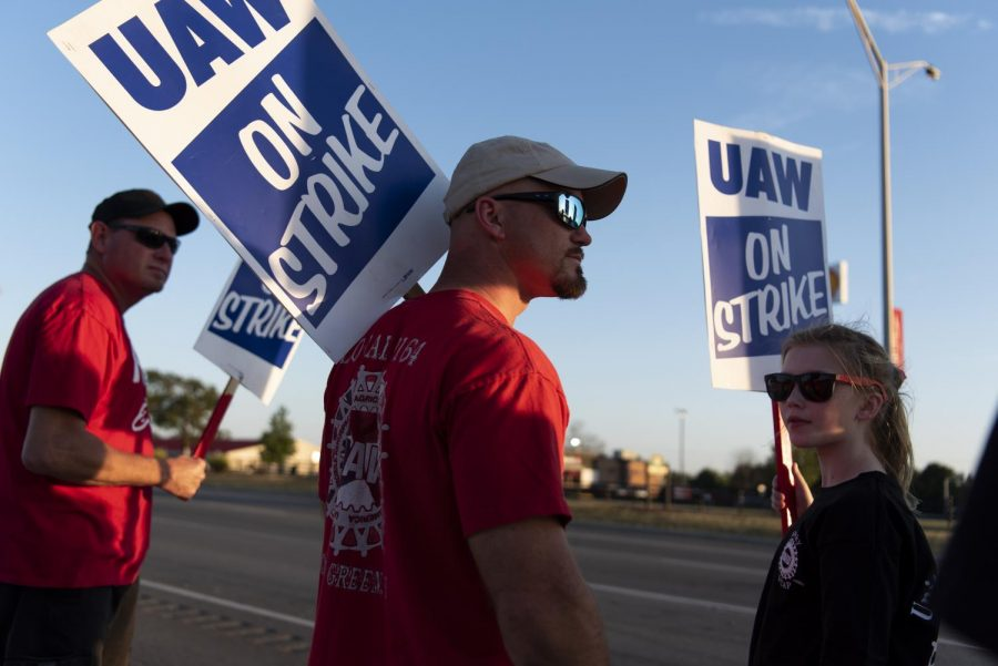 """Kyle Goins, a UAW union representative, stands in a picket line against General Motors with his daughter Greenlee Goins ,13, Saturday Sep. 21, 2019. """"I walked the picket line with my old man and she's doing it with hers,"""" said Goins as he introduced his daughter to other protesters."""