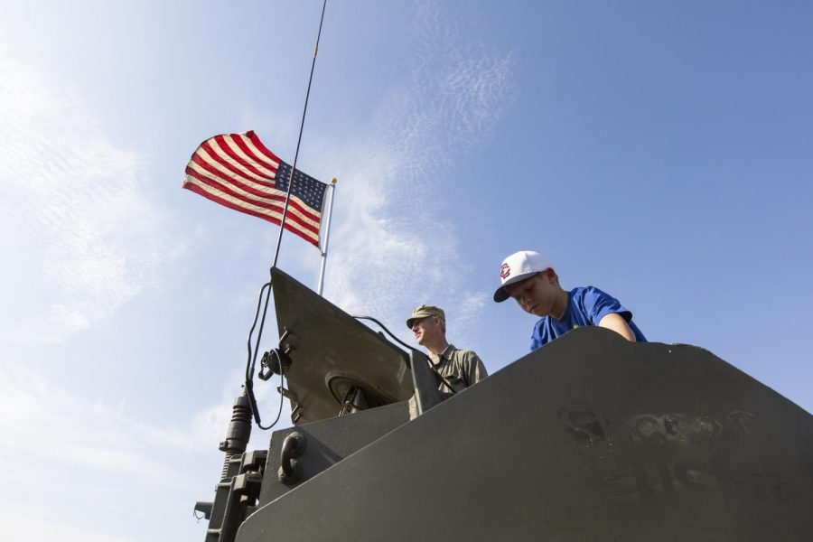 """James Garrett and visitors stand on a World War II tank before the reenactment of the battle known as """"Operation Anvil"""" at Phil Moore Park on Saturday, Sep. 28, 2019. Garrett operated the tank during the reenactment."""
