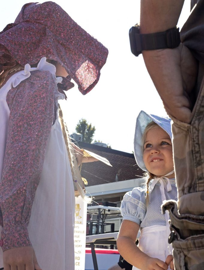 """Annie Roberts, 3, smiles at her sister, Allie, 5, at the Lincoln Days festival in Hodgenville on Saturday, Oct. 5, 2019. Their grandmother, Diane """"Gigi"""" Roberts, sewed the costumes they wore for the Lil' Abe and Sarah Contest which they won third place in."""