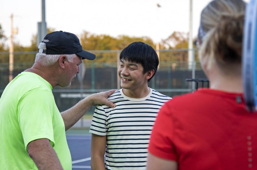 Samuel Chang talks with his tennis coach, Rob Balge, during his weekly tennis lessons at Kereiakes Park on Sept. 29, 2019. Tennis is the first sport Chang has ever played, and Balge said he can really see him improving so far.