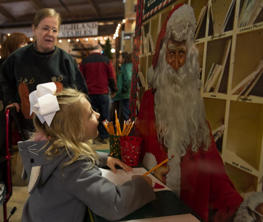 Linley Boykin, 5, stops to write a Christmas list to Santa with her grandmother and great-grandmother on Saturday, Nov. 9, 2019, at the GypsyMoon Marketplace, which hosted a Christmas market weekend.