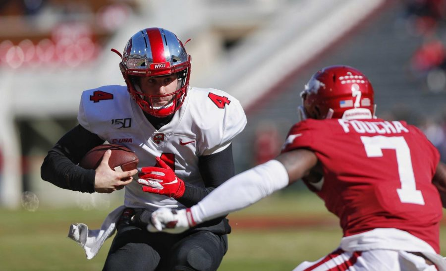 WKU+quarterback+Ty+Storey+%284%29+attempts+to+avoid+the+waiting+arms+of+Arkansas+defensive+back+Joe+Foucha+%287%29+during+the+Hilltoppers%27+45-19+road+win+against+Arkansas+in+Donald+W.+Reynolds+Razorback+Stadium+on+Saturday%2C+Nov.+9%2C+2019.