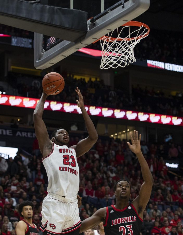 WKU center Charles Bassey (23) rises up for a dunk over Louisville Center Steven Enoch (23). The Cardinals defeated the Hilltoppers 71-54 in Bridgestone Arena on Sunday, Nov. 17 2019, in Nashville.