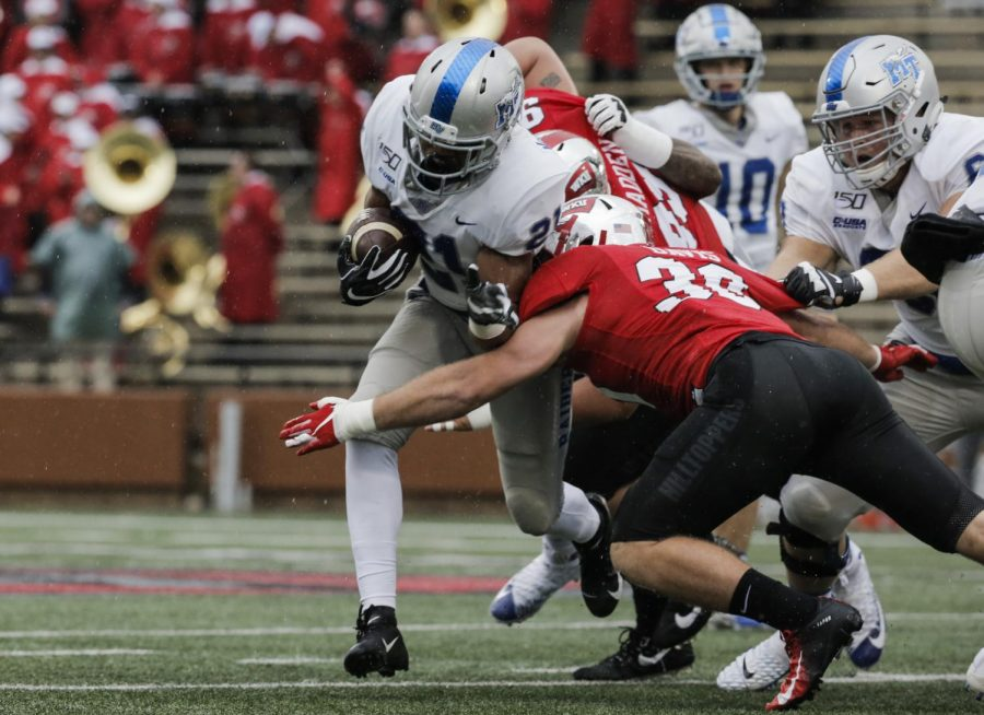 MTSU+junior+running+back+Jayy+McDonald+%2821%29+is+tackled+while+running+with+the+ball+by+WKU+redshirt+junior+Clay+Davis+%2830%29+and+junior+defensive+lineman+Jalen+Madden+%2899%29+during+the+game+against+MTSU+in+L.T.+Smith+Stadium+on+Saturday%2C+Nov.+30%2C+2019.