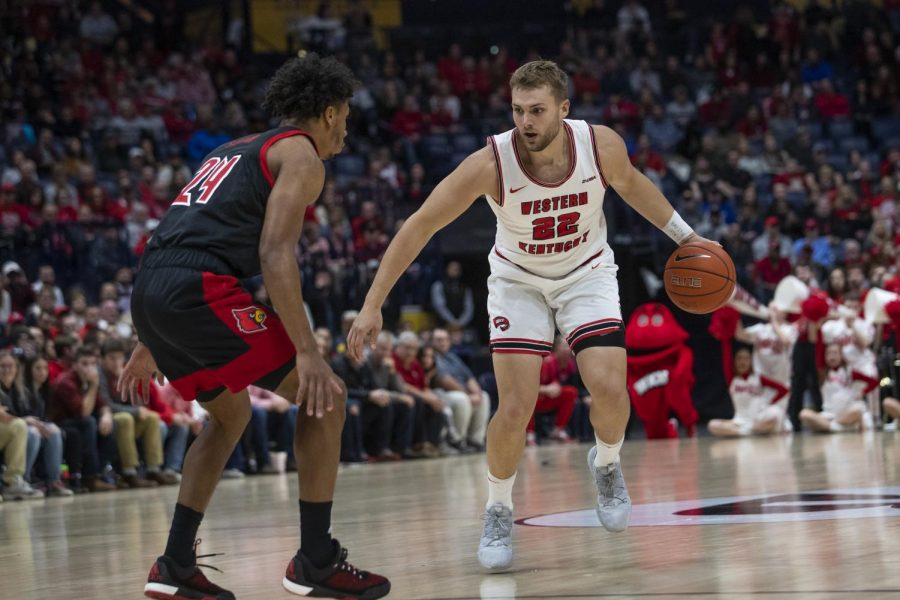 WKU forward Carson Williams (22) drives in guarded by Louisville forward Dwayne Sutton (24). The Cardinals defeated the Hilltoppers 71-54 in Bridgestone Arena on Sunday, Nov. 17 2019, in Nashville.