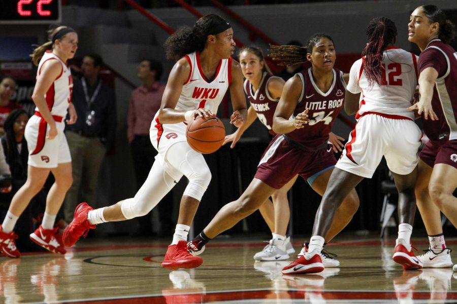 WKU foward Dee Givens (4) use the screen from Fatou Pouye (12) to dribble toward the top of the key. The Lady Hilltoppers defeated Little Rock 77-58 on November 24, 2019 at E.A. Diddle Arena.