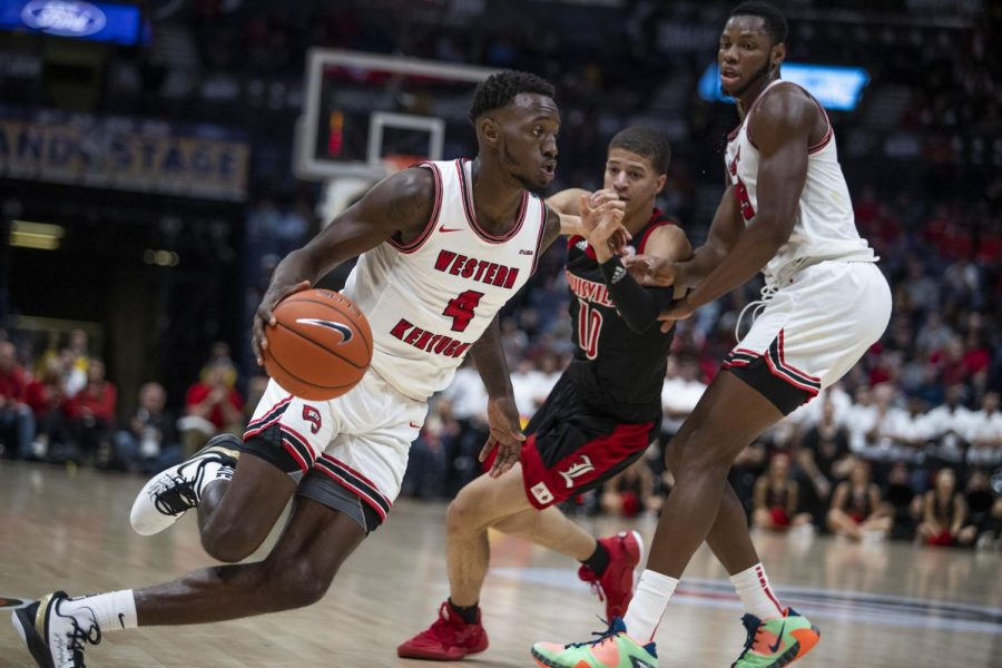 WKU guard Josh Anderson (4) drives to the lane after center Charles Bassey (23) sets a screen on Louisville guard Samuell Williamson (10). The Cardinals defeated the Hilltoppers 71-54 in Bridgestone Arena on Sunday, Nov. 17 2019, in Nashville.