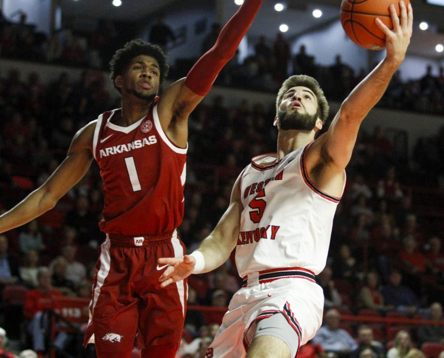 WKU guard Camron Justice (5) goes up for a layup over Arkansas guard Isaiah Joe (1). The Hilltoppers defeated the Razorbacks 86 - 79 in Diddle Arena on Saturday, December 7, 2019.
