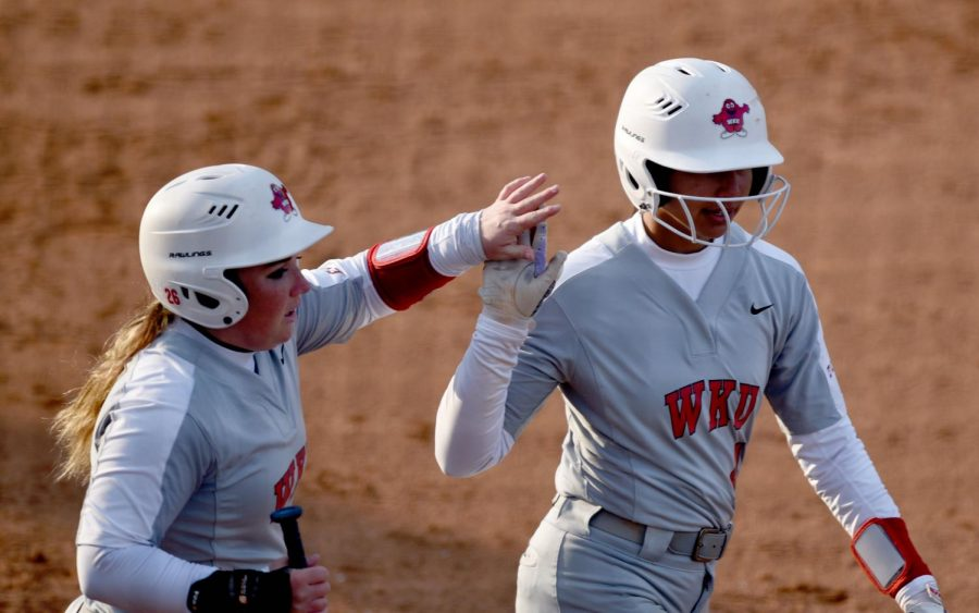 WKU outfielders Paige Carter (26) and Kennedy Sullivan (4) high five after they made two consecutive runs together in one play during the WKU v MTSU softball game on Mar. 6, 2020 at the WKU Softball Complex. The Hilltoppers won 3-1.