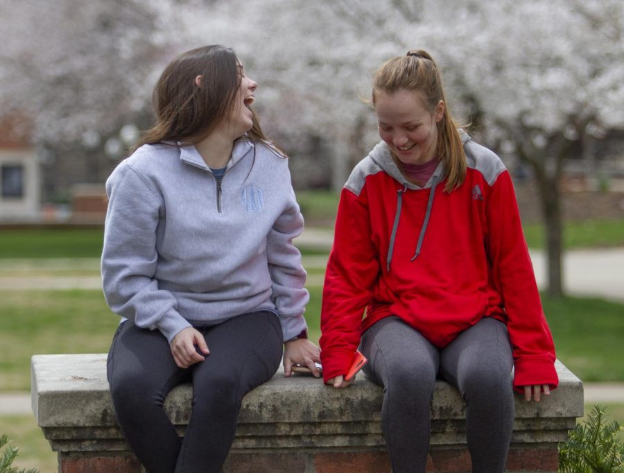 """Gabrielle Sledge (left), a health science major and Anna Gibson, a nursing major, sit in Centennial Park at WKU on March 22, 2020. Both Gibson and Sledge agreed that the state's government and universities are handling the crisis effectively. """"Andy Beshear's killed it,"""" Sledge said."""