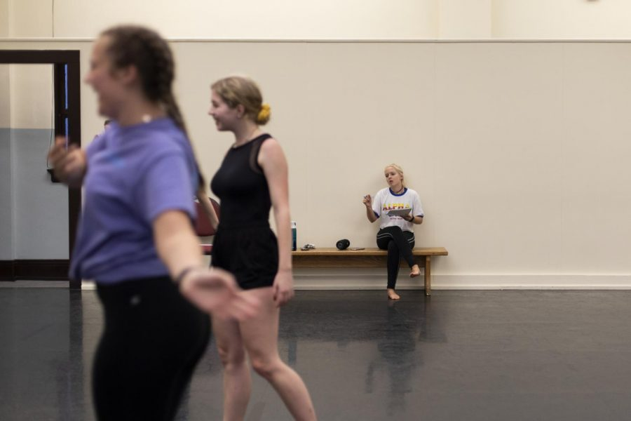 Heather Hartlage, choreographer for NDEO's Kick the Clock, listens to the music and brainstorms ideas alone while her cast dances around her to the music in one of the dance studios in Gordon Wilson Hall of Friday evening, Sep. 6, 2019. Some of the dancers warm up quietly while others laugh and dance around with their friends.