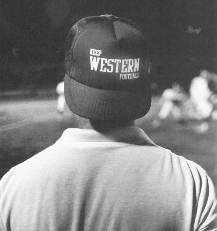 Sporting a hat that mirrored the attitudes of many Western football fans, Daily News Sports Editor Joe Medley watches the Red-White scrimmage game from the sidelines.