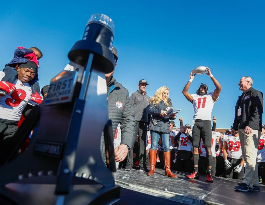 WKU receiver Lucky Jackson raises the MVP football in celebration after breaking his own record of receptions during the First Responders Bowl.