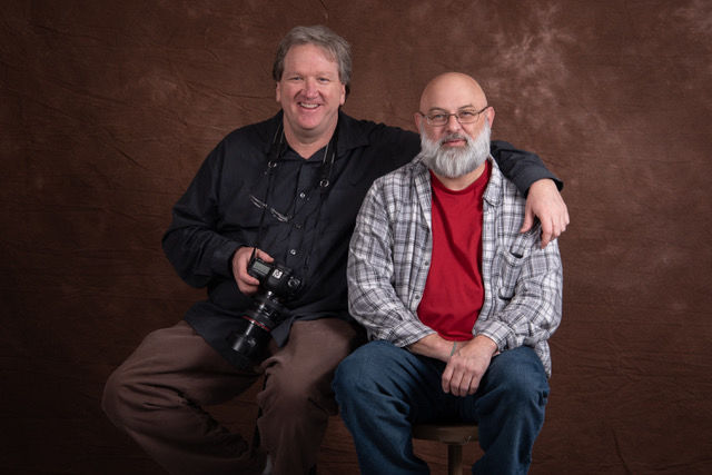 WKU Faculty member Jonathan Adams, left, poses with his student Dave Allen as they test the lighting for a photo booth at the annual Warren County Health Serviced Fair for Refugee and Immigrant Families.Dave Allen who died on May 2, 2020 was volunteering with other WKU Photojournalism student to document the families at the event.Photo by Dalton Puckett