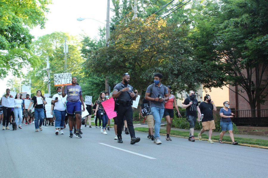 Officer Tim Gray of the WKU Police Department walking alongside protestors.