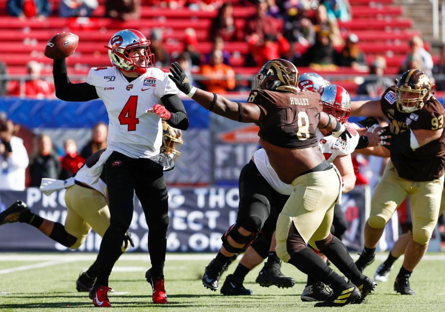 WKU quarterback Ty Storey evades pressure from Western Michigan's defensive line to target Lucky Jackson on the throw.