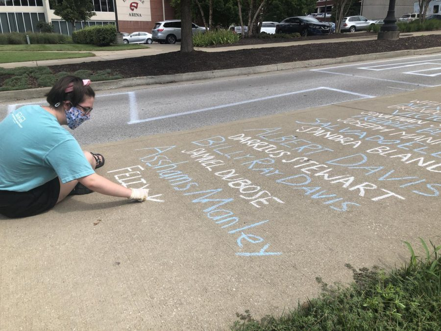Laurel Philpott adds names to the list of victims of racial violence on the sidewalk.