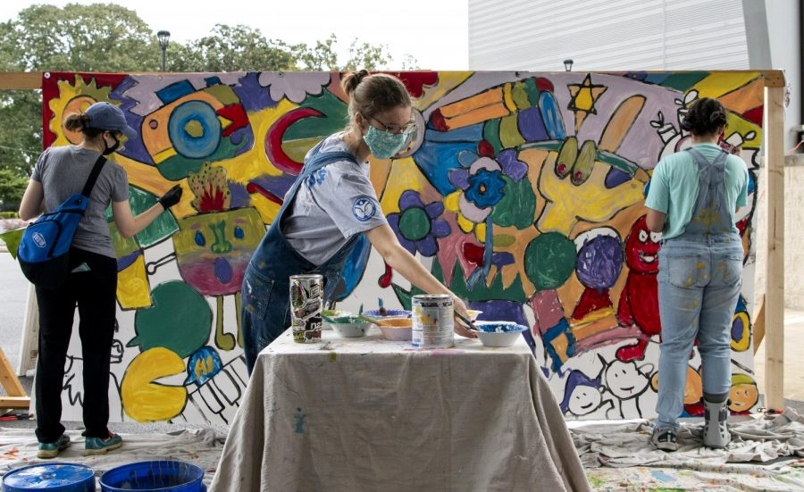 Megan Meredith, left, Gracie Nelson, center, and Annabeth Nelson, right, fill in color on the mural at SOKY Marketplace on Sept. 26, 2020. Grace and Annabeth came with their sister Ella Kate.