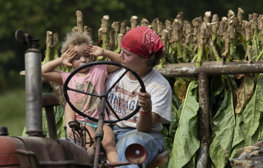 WKU senior Cecilia Morris holds Josie Rhodes while driving a tractor carrying tobacco leaves on Sept. 12, 2020. Morris is a family friend that has been around the farm ever since she was in high school.