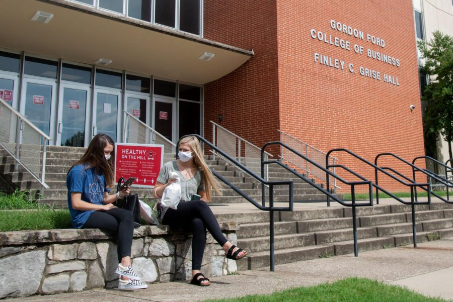 Mallory Bowels (left), freshman, talks to her mom on her phone as her friend Emily Tribus, freshman, waits beside her outside of Grise Hall on the afternoon September 5. Thought campus is typically more populated with students on a early Friday afternoon, many classes have moved online or set social distancing precautions surrounding dismissal times. Dismissing class a few minutes early, for instance, faculty aims to lighten the flow of student traffic and crowding on campus in an effort to stop any spread of COVID-19.