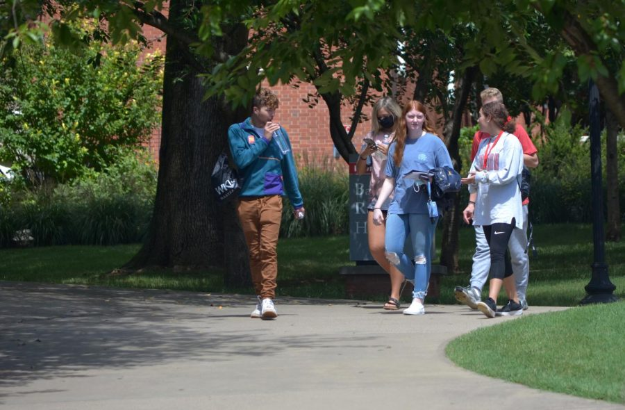 A group of WKU students walk across campus together, most not wearing masks despite WKU's requirement to do so, on Aug. 22, 2020.
