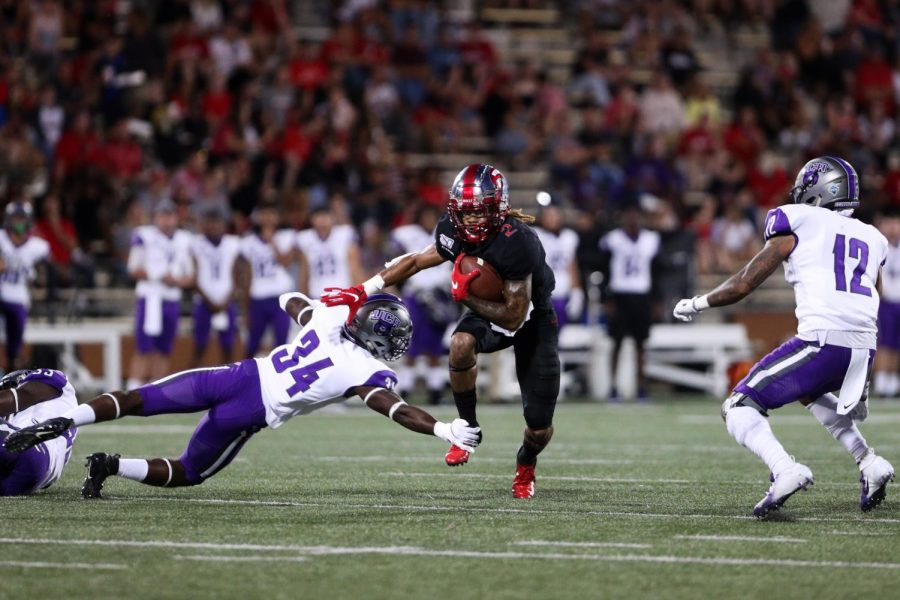 WKU Hilltoppers redshirt junior defensive back Jacquez Sloan attempts to pass with the ball before getting tackled by Central Arkansas defensive back Steven Mackey Jr (34) and Central Arkansas defensive back Isaiah Macklin (12) during WKU's 35-28 loss against Central Arkansas Bears in Houchens Smith Stadium on August 29, 2019.