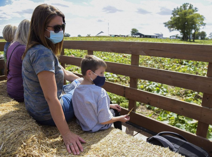 """Ashley Crocker sits with her son, Dylan, on a hayride at Just Piddlin' Farm and Pumpkin Patch in Auburn, Ky., on Friday, Oct. 1. Ashley said she and Dylan visited Just Piddlin' """"to get out of the house."""""""