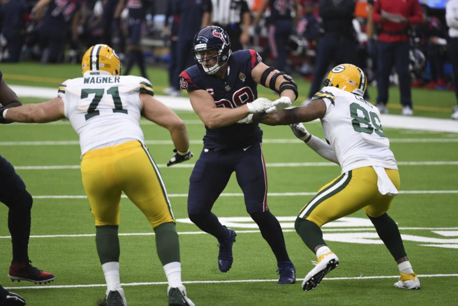 Houston Texans defensive end J.J. Watt, center, rushes up field between Green Bay Packers offensive tackle Rick Wagner (71) and tight end Marcedes Lewis, right, during the first half of an NFL football game Sunday, Oct. 25, 2020, in Houston.