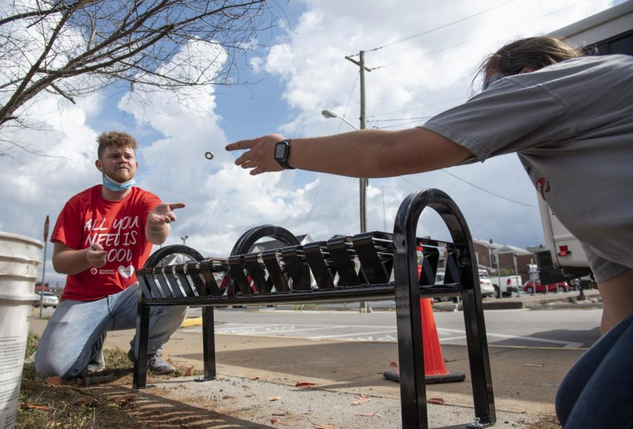 Rebecca+Hurley+%28right%29+tosses+Zachary+Hall+a+washer.+Hurley+and+Hall%2C+both+engineering+majors+at+WKU%2C+were+installing+benches+with+some+of+their+classmates+at+a+bus+stop+on+Center+Street.+Hall+said+the+benches+were+being+installed+for+public+transportation+passengers+so+they+don%E2%80%99t+have+to+sit+on+the+ground.