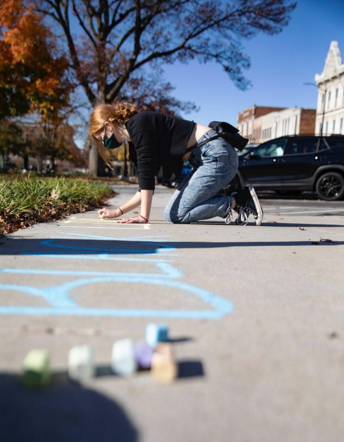Chloe O'Bryan writes 'Black Lives Matter' in chalk at Fountain Square Park as a part of the Racial Justice Education Chalking Movement on Nov. 12, 2020.