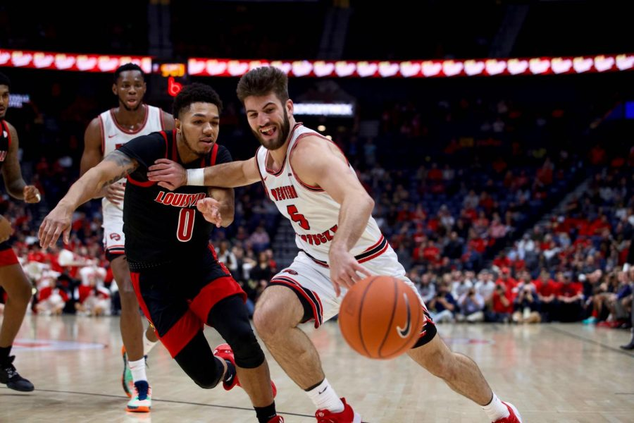 WKU graduate guard Camron Justice (5) battles for a loose basketball with Louisville graduate guard Lamarr