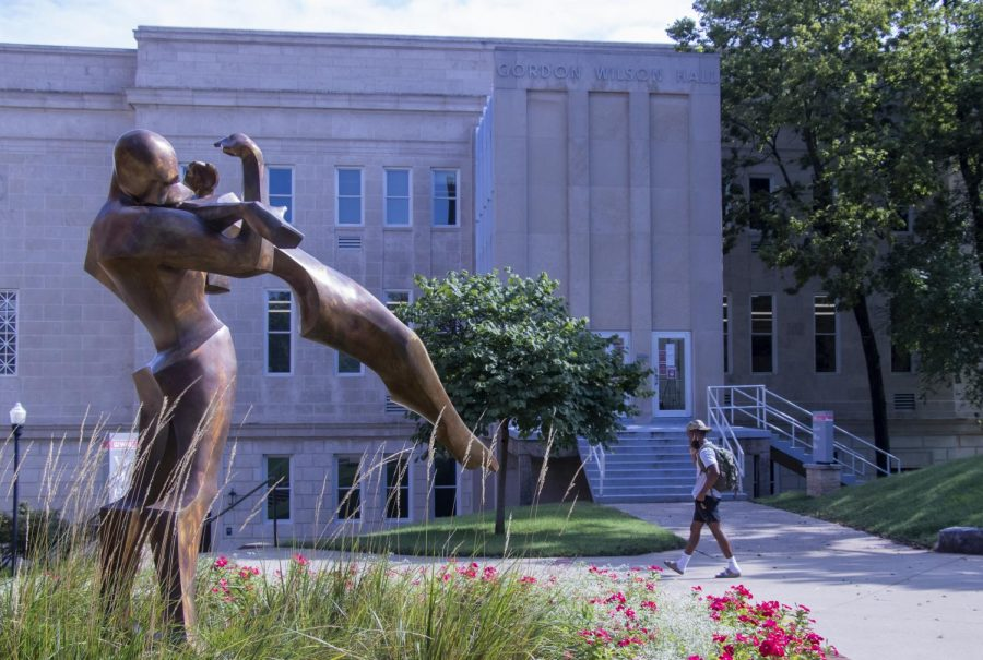"""A student rushes past the """"Trust"""" statue sculpted by Kendra Fleischman located on the top of Western Kentucky University's campus on Monday morning, Aug. 31, 2020. Gordon Wilson Hall, the building behind the student, is home WKU's Theater and Dance Program, who are currently dealing with the struggle of having to have classes in-person while still following COVID-19 guidelines."""