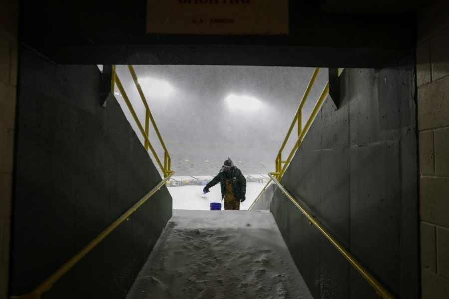 A worker applies salt as snow falls before an NFL football game between the Green Bay Packers and the Tennessee Titans at Lambeau Field Sunday, Dec. 27, 2020, in Green Bay.